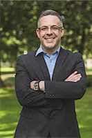 Happy professor looking at camera with arms crossed on campus at the university Stock Photo - Premium Royalty-Freenull, Code: 6109-07497721