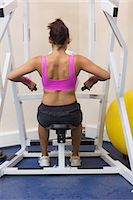 slim - Toned brunette training her arms in weights room of gym Stock Photo - Premium Royalty-Freenull, Code: 6109-07497881