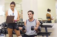 slim - Trainer taking notes of attractive man lifting dumbbells in weights room of gym Stock Photo - Premium Royalty-Freenull, Code: 6109-07497938
