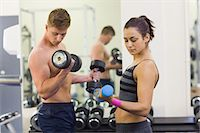slim - Determined man and woman holding dumbbells in weights room of gym Stock Photo - Premium Royalty-Freenull, Code: 6109-07497947