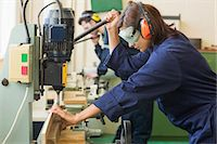 Trainee with safety glasses drilling wood in workshop Stock Photo - Premium Royalty-Freenull, Code: 6109-07497987