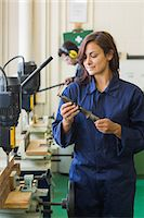 Happy trainee holding tool in workshop Stock Photo - Premium Royalty-Freenull, Code: 6109-07497992