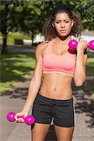 slim - Portrait of a fit young woman exercising with dumbbells in the park Stock Photo - Premium Royalty-Freenull, Code: 6109-07498020