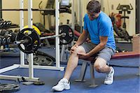 Full length of a healthy young man with an injured leg sitting in the gym Stock Photo - Premium Royalty-Freenull, Code: 6109-07498065
