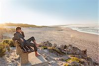 people sitting on bench - Man relaxing on beach bench Stock Photo - Premium Royalty-Freenull, Code: 649-07520095