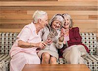 Senior women friends laughing on sofa Stock Photo - Premium Royalty-Freenull, Code: 649-07520305