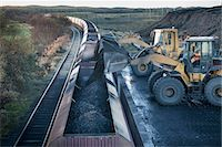 Diggers loading coal onto train at surface coal mine at dawn Stock Photo - Premium Royalty-Freenull, Code: 649-07520487