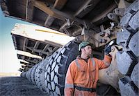 Coal miner inspects dumper truck tyre tread in surface coal mine Stock Photo - Premium Royalty-Freenull, Code: 649-07520494