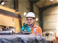 Apprentice engineer inspecting equipment in surface coal mine Stock Photo - Premium Royalty-Freenull, Code: 649-07520538