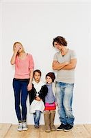 Studio shot of couple with son and daughter in oversize clothes Stock Photo - Premium Royalty-Freenull, Code: 649-07520654