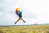 Teenage girl in field with umbrella Stock Photo - Premium Royalty-Freenull, Code: 649-07520738
