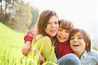 Sister and younger brothers sitting in grassy field Stock Photo - Premium Royalty-Freenull, Code: 649-07520758