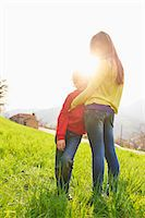 Young boy and older sister in grassy field Stock Photo - Premium Royalty-Freenull, Code: 649-07520762