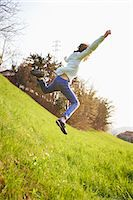 Young boy jumping down steep grassy field Stock Photo - Premium Royalty-Freenull, Code: 649-07520763