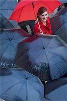 people with umbrellas in the rain - Young woman with red umbrella amongst black umbrella's Stock Photo - Premium Royalty-Freenull, Code: 649-07520862