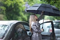 people with umbrellas in the rain - Young woman struggling to put up umbrella Stock Photo - Premium Royalty-Freenull, Code: 649-07520863