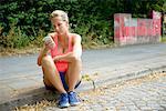 Young female runner sitting on sidewalk using cellphone