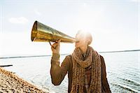 Young woman using megaphone by lake Stock Photo - Premium Royalty-Freenull, Code: 649-07521116