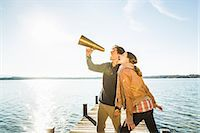 Couple using megaphone by lake Stock Photo - Premium Royalty-Free, Artist: Ikon Images, Code: 649-07521117