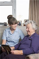 Personal care assistant looking at photograph with senior woman Stock Photo - Premium Royalty-Freenull, Code: 649-07521167