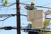 Power engineer in lift bucket working on power lines, Braintree, Massachusetts, USA Stock Photo - Premium Royalty-Freenull, Code: 6105-07521406