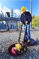 Power engineer entering manhole at a high voltage power distribution station, Braintree, Massachusetts, USA Stock Photo - Premium Royalty-Freenull, Code: 6105-07521410