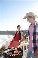 Man and woman tending barbecue with ocean in background Stock Photo - Premium Royalty-Freenull, Code: 635-07522001