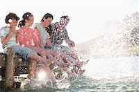 Family on dock splashing feet in lake Stock Photo - Premium Royalty-Freenull, Code: 635-07522051