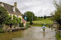 Man wades through flood water in Swinbrook, Oxfordshire, England, United Kingdom Stock Photo - Premium Rights-Managed, Artist: Robert Harding Images, Code: 841-07523521