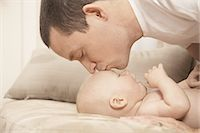 father son shirtless - Father kissing baby's forehead. Stock Photo - Premium Royalty-Freenull, Code: 618-07524208