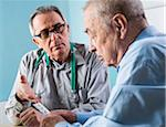 Senior, male doctor conferring with senior, male patient in office, discussing medication, Germany