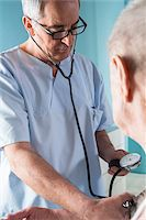 Senior, male doctor taking blood pressure of senior, male patient, in office, Germany Stock Photo - Premium Rights-Managednull, Code: 700-07529245