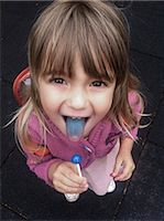 A little girl holding a blue sucker and showing off her blue tongue proudly Stock Photo - Premium Royalty-Freenull, Code: 653-07538976