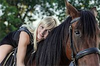 Young woman lying on horse Stock Photo - Premium Royalty-Freenull, Code: 653-07539108