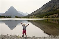 Toddler stands in mountain lake with arms raised Stock Photo - Premium Royalty-Freenull, Code: 6106-07539219