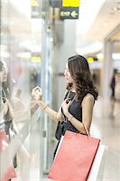 people on mall - young woman looking through a shop window Stock Photo - Premium Royalty-Freenull, Code: 6106-07539531