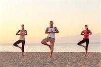 People practising yoga on beach, tree pose Stock Photo - Premium Royalty-Freenull, Code: 6115-07539720