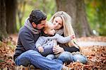 Family with son sits among autumn leaves, Osijek, Croatia