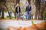 Family with one child taking a walk in autumn, Osijek, Croatia