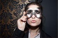 Woman wearing party mask, pursing lips, portrait Stock Photo - Premium Royalty-Freenull, Code: 632-07539881