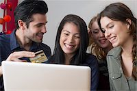 Friends gathered around laptop computer preparing to use credit card for online purchase Stock Photo - Premium Royalty-Freenull, Code: 632-07539950