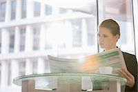 Businesswoman reading newspaper at office cafeteria Stock Photo - Premium Royalty-Freenull, Code: 693-07542122