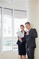 Businessman using digital tablet with female colleague in office Stock Photo - Premium Royalty-Freenull, Code: 693-07542148