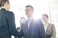 Confident business partners shaking hands in office Stock Photo - Premium Royalty-Freenull, Code: 693-07542183