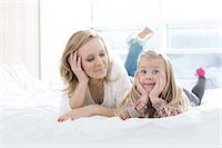 Mother looking at cute daughter making faces while lying in bed Stock Photo - Premium Royalty-Freenull, Code: 693-07542247