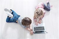 High angle view of brother and sister using laptop on floor at home Stock Photo - Premium Royalty-Freenull, Code: 693-07542256