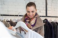 selecting - Smiling young woman choosing sweater in store Stock Photo - Premium Royalty-Freenull, Code: 693-07542295