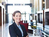 Businesswoman smiling in lobby Stock Photo - Premium Royalty-Freenull, Code: 6113-07542607