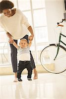 Mother helping baby boy walk in living room Stock Photo - Premium Royalty-Freenull, Code: 6113-07542842