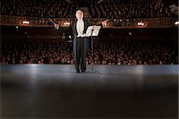 Conductor performing on stage in theater Stock Photo - Premium Royalty-Freenull, Code: 6113-07542916